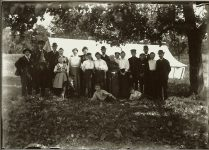 A group of twenty-one standing people under trees out in the country EW Carter photo ca. 1900 Glass negative: 7″x5″