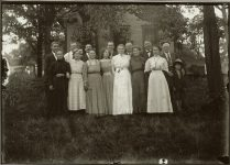 "A group of fifteen standing people, outside a small wood building, out in the country. Note ""Huck Finn"" on the right. EW Carter photo ca. 1900 Glass negative: 7″x5″"