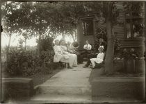 "Family of seven sitting outside listening to a portable ""Victrola"" EW Carter photo ca. 1900 Glass negative: 7″x5″"