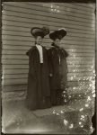 Two girls, with big hats, standing on a boardwalk. EW Carter photo ca. 1900 Glass negative: 5″x7″