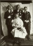 Three boys and a girl standing inside all dressed up in white gloves. EW Carter photo ca. 1900 Glass negative: 5″x7″