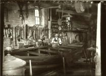 A boat-builder inside his shop with frame of a small boat. EW Carter photo ca. 1900 Glass negative: 7″x5″
