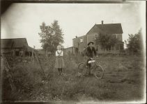 A girl and young man on a bicycle on farm. EW Carter photo ca. 1900 Glass negative: 7″x5″