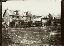 Street scene featuring the Wines & Liquors Cigars & Tobacco. Probably somewhere near Kalispell, Montana EW Carter photo ca. 1900 Glass negative 2: 7″x5″